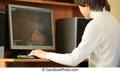 Gamer child playing computer games on desktop pc at home