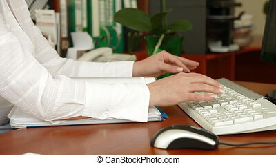 Business woman typing on keyboard at a desk in the bank office