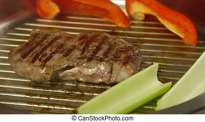 Beef steak grilled with vegetables on frying pan