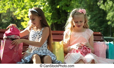 Fashion little girls with shopping bags on a bench - Fashion...