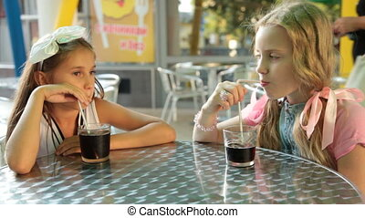 Children drinking cola drink at outdoor cafe