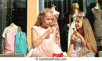 Fashion little girls  eating ice cream in front of clothing store shop window