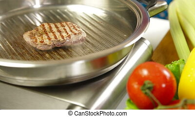 Beef meat steak frayed on a frying pan closup