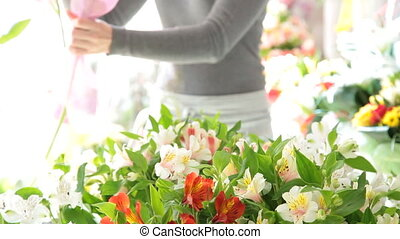 Woman making a bouquet of fresh flowers in a flower shop