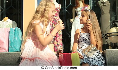 Fashionable little girls in summer dresses in front of clothing store