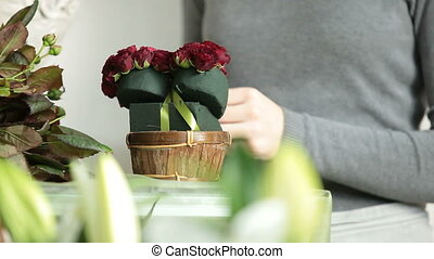 Woman making a flower arrangement of red roses in the form...