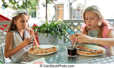 Little girls eating pizza and drinking cola drink at outdoor...