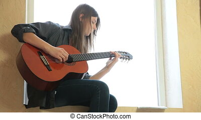 Teen Girl Playing Guitar At Home. Medium Shot