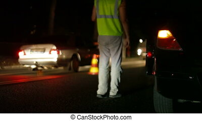Insurance agent assessing damage to vehicle at the accident site at night