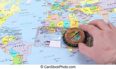 Hand moving a compass over a world map