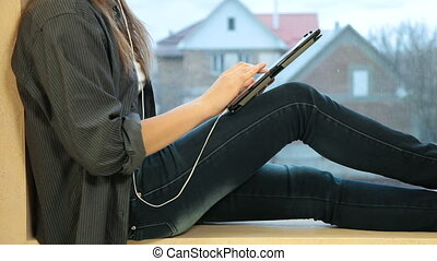 Girl listening to music with tablet computer sitting by...