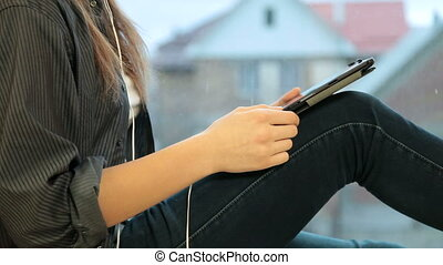 Teenager girl listening music on your digital tablet  sitting by window