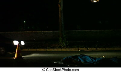 Dead person lying on a street after road accident at night
