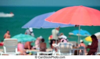 People spending summer vacation on the beach out of focus