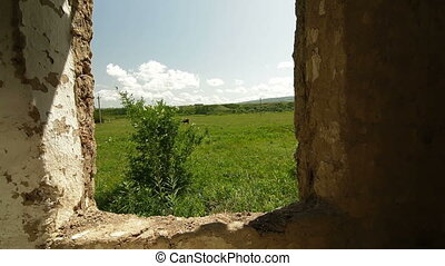 View of rural landscape from the window of old abandoned farm house in summer