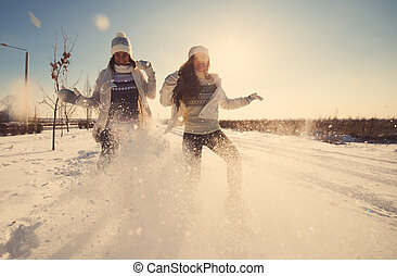 Two girlfriends have fun and enjoy fresh snow at beautiful...