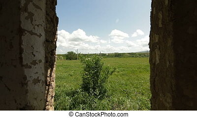 View from the window of abandoned farmhouse at countryside landscape