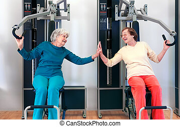 Happy Grannies Enjoying Chest Press Exercise, as if Playing,...