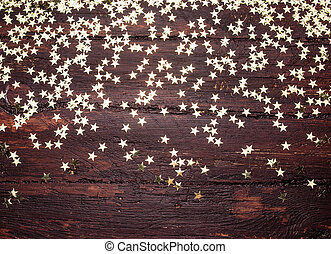Glitter golden stars on grunge wood background. Holiday...