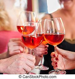 Hands Raising Glasses of Tasty Red Wine - Macro Shot of...