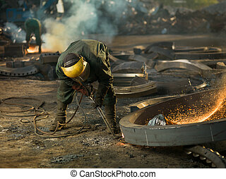 welder on recycling site - worker with protective equipment...