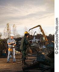 workers at scrap metal junkyard