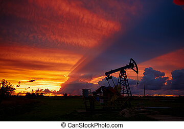 Oil derricks on a background of beautiful sunset,...