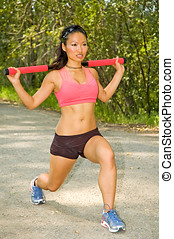 Weight bar lunge - Young Asian woman doing lunges with a...