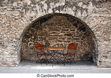 Cafe table against the ancient wall.