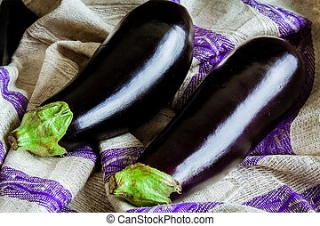 two raw organic eggplant on sackcloth - two raw organic...
