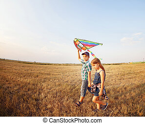 Happy boy and little girl with bright kite on a meadow in a...