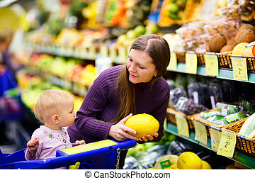 Family in supermarket - Young mother with baby daughter...