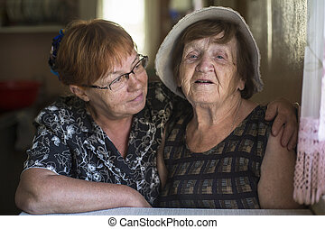 Portrait of old woman and her daughter in the house.