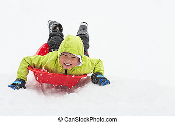 Boy on Sledge - Cute young boy smiling while he is sledging