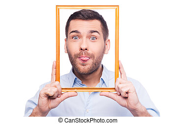 Playful portrait Handsome young man in shirt sticking his tongue out and holding picture frame in front of his face while standing against white background