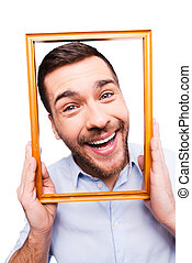 Joyful frame. Handsome young man in shirt holding picture frame in front of his face and smiling while standing against white background