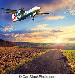 colorful sunset over road with plane in the sky