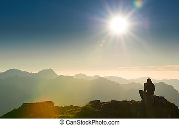 lonely sad person sits on summit of mountain at sunset