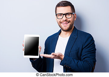 Copy space on his tablet. Cheerful young man showing a digital tablet and smiling while standing against grey background