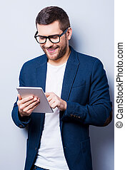 Examining his brand new tablet. Cheerful young man working on digital tablet and smiling while standing against grey background