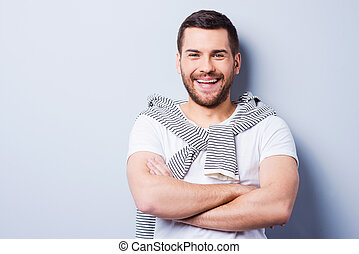 Cheerful and handsome Portrait of young man keeping arms...