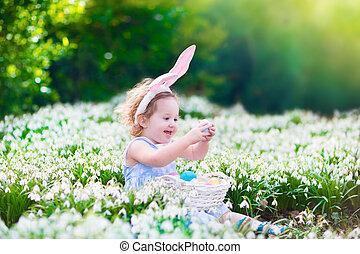 Little girl on Easter egg hunt - Adorable curly toddler girl...