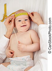 Doctor measuring the Head circumference of a Baby - A Doctor...