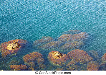 Water surface and stones - transparent coastal azure water...