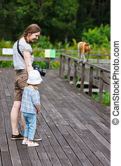 Mother and daughter looking at proboscis monkey on Borneo...