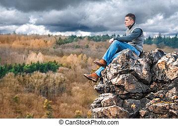 Tourist hiker man sitting on the rock in mounatin