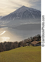 Sunrise in a village over the Thun lake in Swiss Alps in...