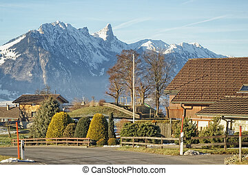 Swiss village with a view to the Alps mountains near the...