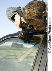 paparazzi - The man with the camera has hidden on a car roof...