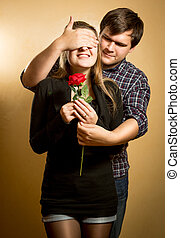 young man closing girlfriends eyes and giving her red rose -...
